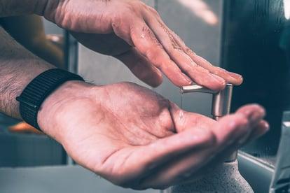 Hands pumping soap dispenser