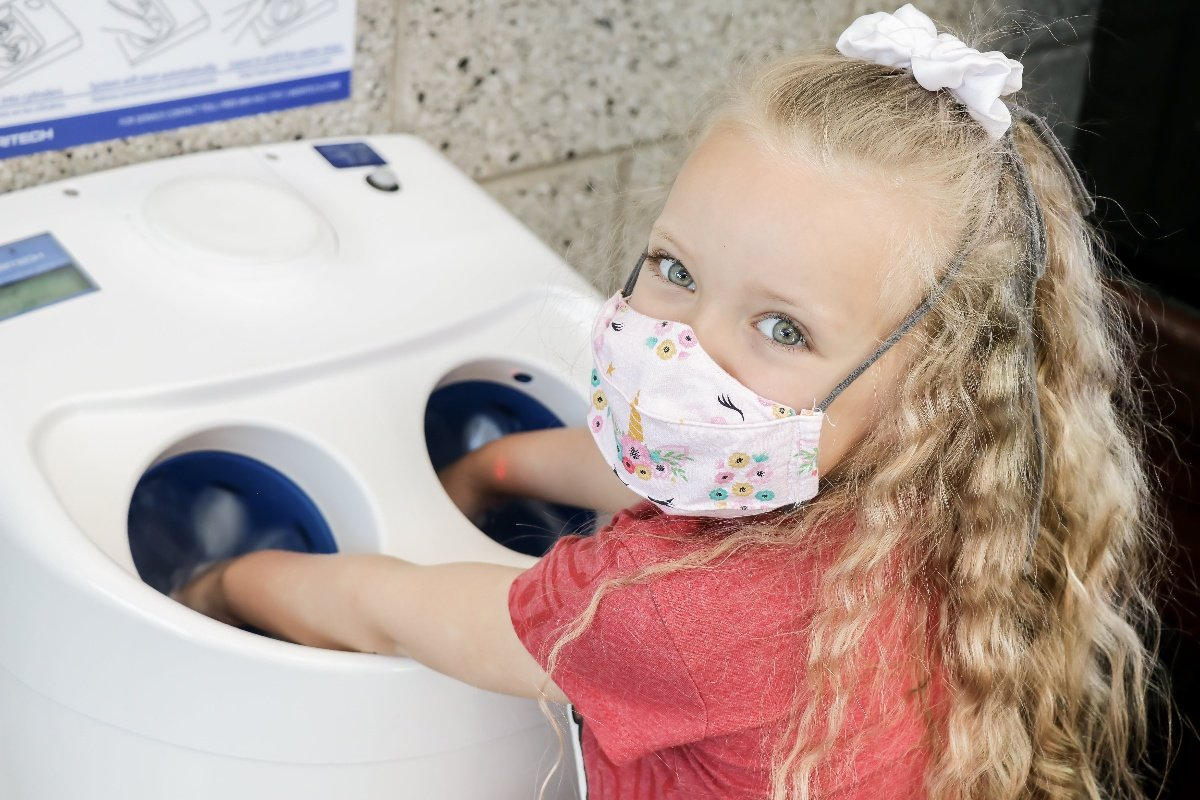 Girl using a CleanTech Hand Wash Station at a School
