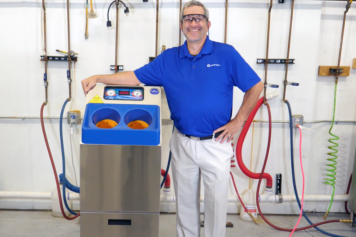 Man standing next to a CleanTech hand sanitation station